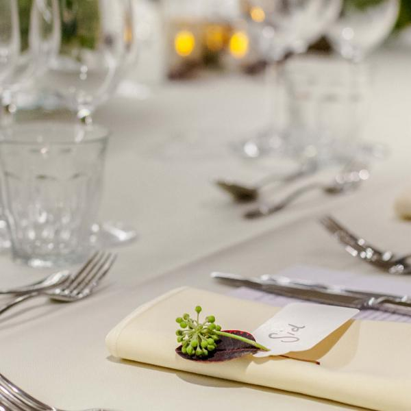 Elegant table setting with silver cutlery, cream tablecloth and crystal glassware